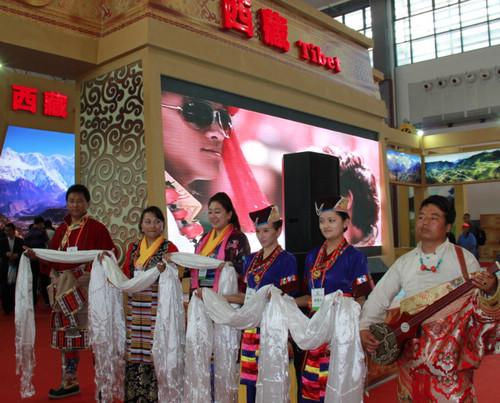 中国 台前/展台前热情的藏族人民为参观的游客献上舞蹈和哈达