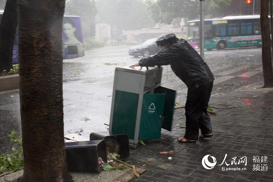 台风登陆后,雨势加大,福州市环卫工作人员正在处理被风吹倒的垃圾桶。 人民网福建频道焦艳 摄