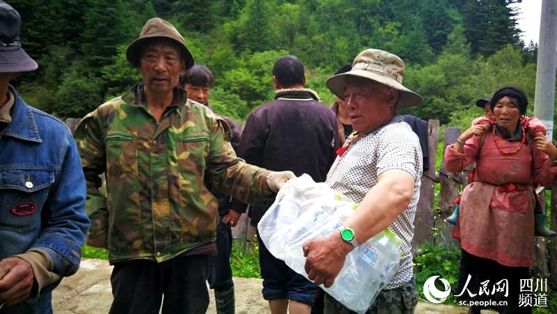 泽旺扎西老人搬运泥土包。(汪子娟 摄)