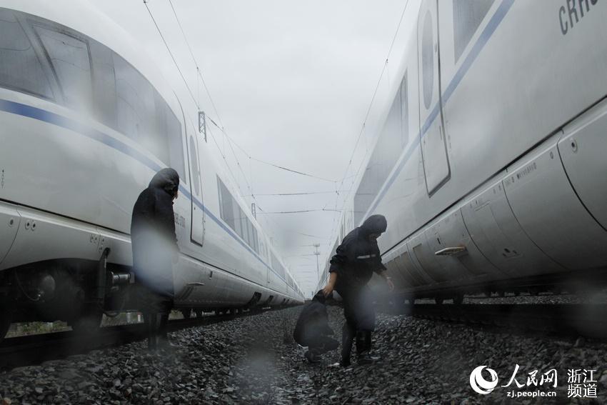 温州苍南所民警冒雨检查停运列车车底。