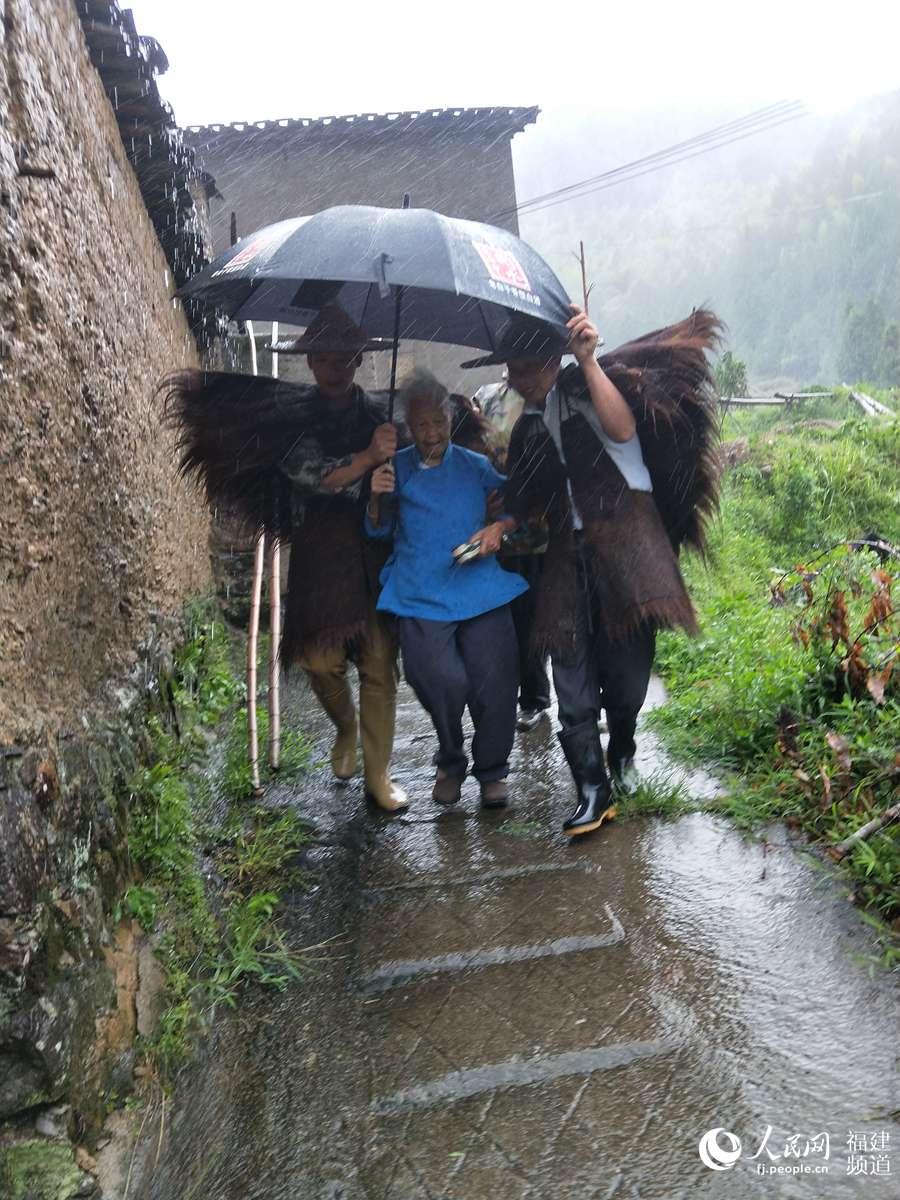 福建周宁李墩镇楼坪村干部搀扶着老奶奶转移至避灾点。林茂良摄