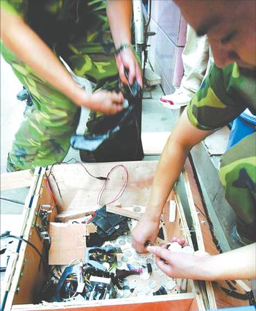 广州/图为执法人员正在从砸烂的老虎机中搜出赌资(资料图片)