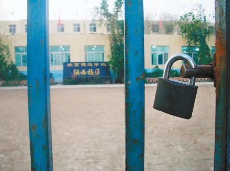 教室 学生/学校大门紧锁,远远可见里面教室的灯亮着,有学生在上课。